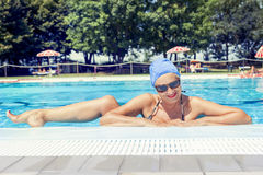 Charming lady in swimsuit posing by the poolside. In summer. Concept of beautiful people having fun in summertime Stock Photos