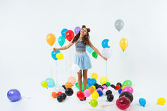 Charming lady in trendy clothing looks happy holding balloon bunch Royalty Free Stock Image