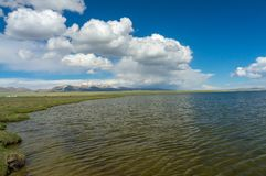 Charming lake with delightful clouds. Charming mountain lake Son-Kul, with delightful clouds and blue sky Stock Images