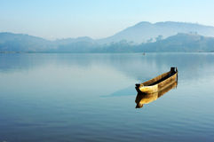 Charming landscape with lonely wooden boat (dug-out canoe ) on l Royalty Free Stock Images