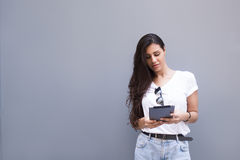 Charming latin woman holding her digital tablet computer while standing against street wall background with copy space area for yo. Female using touch pad in Royalty Free Stock Photo