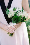 Charming lily of the valley wedding bouquet in hands of the bride. Charming lily of the valley wedding bouquet in the hands of the bride with no face Royalty Free Stock Image