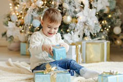 The charming little boy baby sits near a Christmas tree with gif Stock Photo