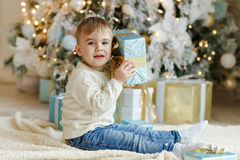 The charming little boy baby sits near a Christmas tree with gif Royalty Free Stock Photos