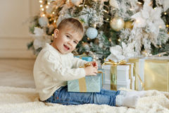 The charming little boy baby sits near a Christmas tree with gif Royalty Free Stock Photo