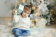 The charming little boy baby sits near a Christmas tree with gif Stock Image