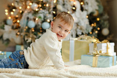 The charming little boy baby sits near a Christmas tree and smil Stock Images