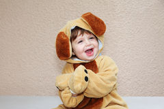The charming little boy cheerfully laughs. The charming little boy in a fluffy suit for a carnival with long ears cheerfully laughs Royalty Free Stock Image