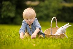 Charming little boy hunting for easter egg in spring park on Easter day. Cute little child with traditional bunny celebrating feast outdoors royalty free stock image