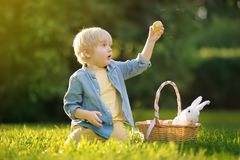Charming little boy hunting for easter egg in spring park on Easter day. Cute little child with traditional bunny celebrating feast outdoors stock image