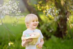 Charming little boy hunting for easter egg in spring park on Easter day. Traditional easter festival outdoors stock image