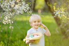 Charming little boy hunting for easter egg in spring park on Easter day royalty free stock image