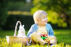 Charming little boy hunting for easter egg in spring park on Easter day Stock Photo