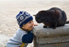 Charming little boy playing with a black cat. Charming little boy smiling while playing with large black cat outdoors stock photo