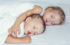 Charming little brother and sister asleep. Embracing on white background Royalty Free Stock Photo