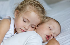 Charming little brother and sister. Asleep embracing on white background Royalty Free Stock Photography