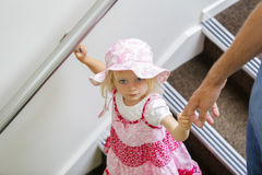 Charming little caucasian girl in pink floral dress looking up , walking downstairs stock photos