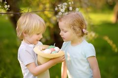Charming little children hunts for painted eggs in spring park on Easter day. Traditional easter festival outdoors royalty free stock photos