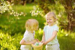 Charming little children hunts for painted eggs in spring park on Easter day. Traditional easter festival outdoors stock photography
