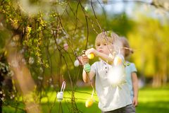 Charming little children hunts for painted eggs in spring park on Easter day. Traditional easter festival outdoors royalty free stock photo