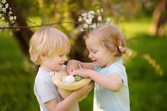 Charming little children hunts for painted eggs in spring park on Easter day stock images