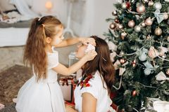 Charming little daughter in nice dress put a flower in mothers hair near the New Year`s tree stock photography
