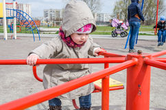 Charming little girl baby riding on a swing in a circle at the amusement park, dressed in a raincoat with a hood, a hat with a bow Stock Photo