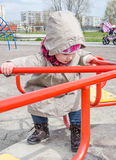 Charming little girl baby riding on a swing in a circle at the amusement park, dressed in a raincoat with a hood, a hat with a bow Royalty Free Stock Image