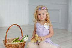 Charming little girl blonde in a dress holding a duckling, in a Stock Photos