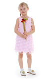 Charming little girl. Charming blonde girl in a pink dress stands with flowers on a white background Royalty Free Stock Photography