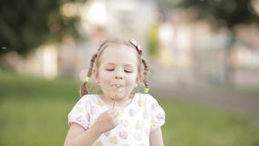 Charming little girl blowing dandelion while walking. Front view of charming little girl in white dress blowing dandelion while walking in park. Funny child stock footage
