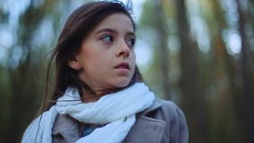 Charming little girl with a brown scared eyes and long brunette hair. A frightened child is standing in the middle of. The forest and looking for something with stock video footage