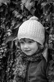 Charming little girl child in a hat and coat standing against the wall with wild grapes sunny autumn day playing and enjoying happ Royalty Free Stock Photo
