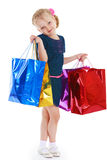 Charming little girl. Cute blonde girl holding large colorful shopping bags, white background Royalty Free Stock Photos