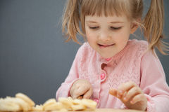 Charming little girl cutting a ripe banana Royalty Free Stock Images