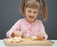 Charming little girl cutting a ripe banana Royalty Free Stock Photography