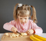Charming little girl cutting a ripe banana Royalty Free Stock Photo