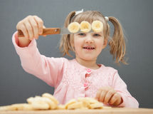 Charming little girl cutting a ripe banana Royalty Free Stock Image