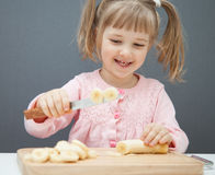 Charming little girl cutting a ripe banana Stock Photography