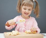 Charming little girl cutting a ripe banana Stock Photography