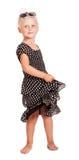 Charming little girl in dark dress with polka dots, isolated. Charming little blond girl in a dark dress with polka dots, bows and sunglasses on her head stock photo
