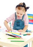 Charming little girl draws with markers while Royalty Free Stock Photo