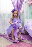 Charming little girl in a dress on horseback Royalty Free Stock Photos
