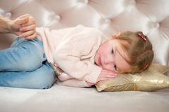 Charming little girl falls asleep on a pink sofa. The mother`s hand caresses the baby stock image
