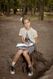 Charming little girl in forest with  book Royalty Free Stock Photo
