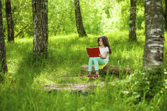 Charming little girl in forest with book sitting on tree stump Stock Photo