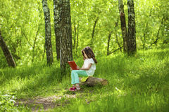 Charming little girl in forest with book sitting on tree stump Royalty Free Stock Images