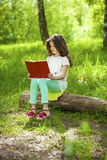 Charming little girl in forest with book sitting on tree stump Stock Photography