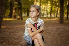 Charming little girl in forest with  doll Stock Images