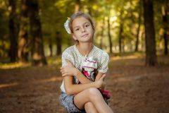 Charming little girl in forest with  doll Royalty Free Stock Images